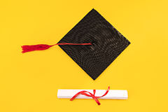 Odgórny widok skalowanie dyplom na żółtym tle i mortarboard zdjęcia royalty free