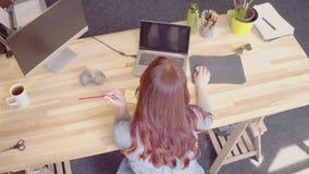 Odgórny widok skwaśniały młody bizneswoman pracuje przy drewnianym stołem zdjęcie wideo