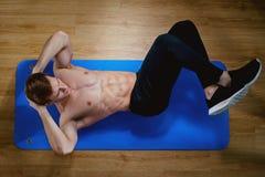Odgórny widok sporty męski facet robi abs ćwiczy na podłoga w th Zdjęcia Royalty Free