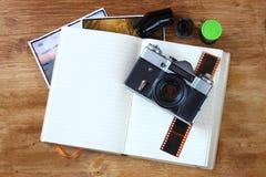 Odgórny widok stara rocznik kamera i obrazki nad drewnianym brown tłem. Zdjęcia Royalty Free
