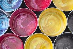 Odgórny widok stare CMYK farby puszki na ciemnym tle Kolorowy bac Fotografia Royalty Free