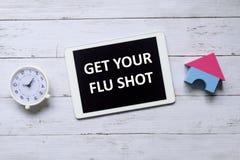 Odgórny widok stołowy zegar i pastylka pisać z Dostajemy Twój szczepionka przeciw grypie na drewnianym tle obraz stock