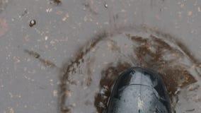 Odgórny widok stopa w czarnym gumowym bucie w kałuży zdjęcie wideo