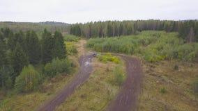 Odgórny widok SUVs jeżdżenie na wiejskiej drodze klamerka Droga ściga się na borowinowych drogach w wiejskim lasowym terenie zbiory wideo