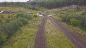 Odgórny widok SUVs jeżdżenie na wiejskiej drodze klamerka Drogi rasa na wiejskim zalesionym terenie na brudnej ziemi zdjęcie wideo