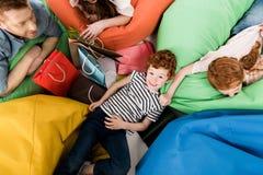 odgórny widok szczęśliwa młoda rodzina odpoczywa na bobowej torbie z torba na zakupy fotografia royalty free