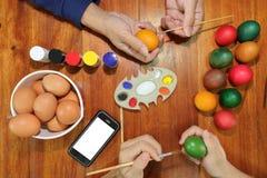 Odgórny widok szczęśliwy chrześcijański rodzinny czas podczas przygotowywa jajka dla Easter dnia Zdjęcie Stock