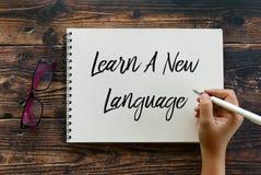 Odgórny widok szkła i ręki mienia pióra pisać Uczy się Nowego języka na notatniku na drewnianym tle zdjęcia royalty free