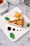 Odgórny widok szklana filiżanka herbata z mennicą, białym czajnikiem, kawałek czekoladowy karmelu tort na półkowym i szarym tle Fotografia Royalty Free