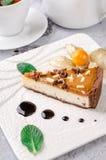 Odgórny widok szklana filiżanka herbata z mennicą, białym czajnikiem, kawałek czekoladowy karmelu tort na półkowym i szarym tle Zdjęcia Stock
