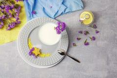 Odgórny widok szklany puchar z mlekiem, talerzem, srebną łyżką i żółtym jaskrawym carambola na świetle, - szary tło zdjęcie stock