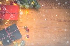 Odgórny widok teraźniejszość, sosen gałąź, Bożenarodzeniowe piłki i światła na drewnianym tle z śnieżną narzutą, zdjęcie stock