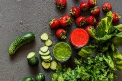 Odgórny widok Truskawkowy smoothie i zieleni smoothie w dwa szkłach z składnikami na szarym tle Detox zdrowy Zdjęcie Stock
