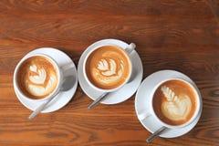 Odgórny widok trzy filiżanki kawy latte sztuki z tulipanu wzorem na drewnianym stole z kopii przestrzenią obraz stock
