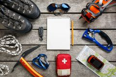 Odgórny widok turystyczny wyposażenie dla halnej wycieczki na nieociosanej lekkiej drewnianej podłoga z notatnikiem wewnątrz i pu zdjęcie stock