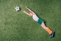 Odgórny widok udaje bawić się piłkę nożną na trawie chłopiec obraz stock