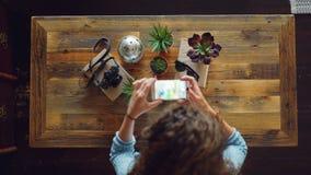 Odgórny widok umieszcza kamerę młoda kobieta, rośliny i okulary przeciwsłoneczni na stole wtedy bierze obrazek z smartphone tworz zbiory