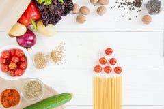 Odgórny widok uncooked makaron z pomidorami i świeżymi surowymi warzywami Obrazy Stock
