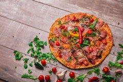 Odgórny widok Włoska pizza na drewnianym stołowym tle Cała kolorowa pizza z gorącym pieprzem i mięsem kosmos kopii Zdjęcia Royalty Free