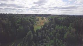 Odgórny widok wiejska droga w lasu i chmury nieba horyzoncie klamerka Mały dom w lesie obok wiejskiej drogi Ustronny życie wewnąt zbiory