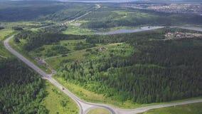 Odgórny widok wiejski rondo klamerka Ruch drogowy na rondo wiejskiej drodze w obszarze zalesionym Miasto na jeziornym brzeg w les zdjęcie wideo