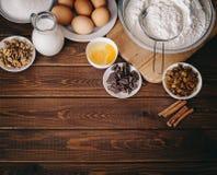Odgórny widok Wypiekowi składniki dla domowej roboty ciasta na nieociosanym drewnianym tle Obraz Stock