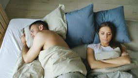 Odgórny widok wzburzona łgarska bezsenna para w łóżku obrażał przez bełta obrazy royalty free