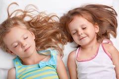 Odgórny widok zadowolone atrakcyjne małe dziewczyny lub siostry my uśmiechamy się wpólnie, śpimy w łóżku, kłamamy blisko each inn zdjęcie stock