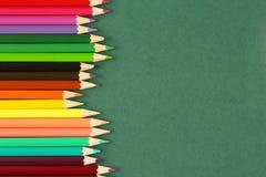 Odgórny widok, zamyka up dużo, jaskrawi wielo- barwioni drewniani ołówki na ciemnozielonym tle z kopii przestrzenią z rzędu Zdjęcie Royalty Free