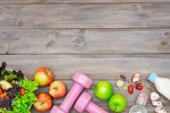 Odgórny widok Zdrowy styl życia pojęcie, sportów equipments i świezi foods na drewnianym tle, Odgórny widok z kopii przestrzenią zdjęcie royalty free