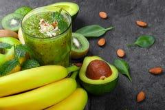 Odgórny widok zdrowy zielony koktajl na zmroku - szarości kamienny tło Wiele tropikalne owoc blisko fruity smoothie zdjęcie stock