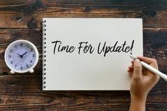 Odgórny widok zegaru i ręki mienia pióro pisze czasie Dla aktualizacji! na notatniku na drewnianym tle zdjęcie stock
