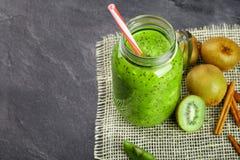 Odgórny widok zielony gęsty koktajl Kiwi smoothie i tropikalne owoc na szarym tle Zimny fruity napój z a zdjęcia royalty free