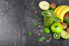 Odgórny widok zielony koktajl i owoc na zmroku - szarości kamienny tło Wiele tropikalne owoc blisko fruity smoothie obrazy royalty free