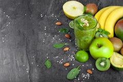 Odgórny widok zielony koktajl i owoc na zmroku - szarości kamienny tło Wiele tropikalne owoc blisko fruity smoothie zdjęcie stock