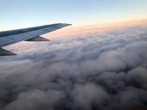 Odgórny widok ziemia od porthole okno samolot na skrzydle z silnikami, turbina i clo, biali puszyści, podeszczowi, obraz royalty free