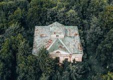 Odgórny widoku z lotu ptaka strzał zaniechany budynek w nieprzejezdnym zwartym zielonym lesie zdjęcia stock
