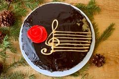 Odgórny widok Czekoladowy tort Z A Stylizuj?cym wizerunkiem Muzykalna Pi?cioliniowa klepka Z Clef I rewolucjonistki ró?a Na Drewn obraz stock