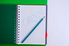 Odg?rny widok otwarty ?limakowaty pusty notatnik z o??wkiem na zielonym biurka tle zdjęcie royalty free