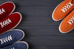 Odg?rny widok przypadkowi kolorowi zamszowy trenery na popielatych drewnianych deskach zdjęcie stock