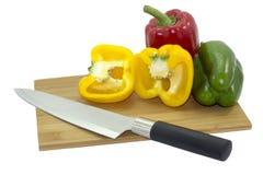 Odizolowywający trzy Dzwonkowego pieprzu na drewnianej tnącej desce z kuchennym nożem Fotografia Royalty Free