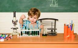 Odkrywa ciecze Praktyczny wiedzy poj?cie Nauki stypendium i dotacje Chłopiec spełniania chemii testa Wunderkind obrazy stock