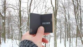 Odkrywa lub podróży pojęcie Ręka trzyma książkę z inskrypcją Na tle zima las zbiory wideo