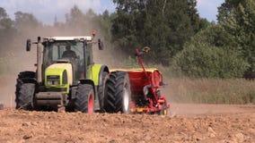 Odlar spridd gödningsmedel för traktoren på fältet i sommar lager videofilmer