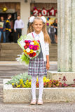 Odlaren behandla som ett barn flickaförsta-väghyveln med buketten av blommor på skolan Royaltyfri Bild