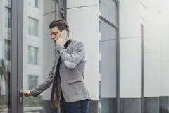 Odległy plan młody biznesowy mężczyzna opowiada telefonem komórkowym i otwiera drzwi fotografia stock