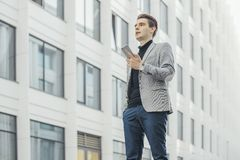 Odległy plan opowiada telefonem komórkowym obok drapacza chmur młody biznesmen obrazy royalty free