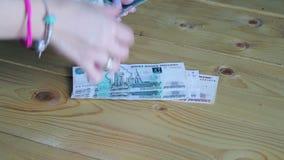 Odliczający pieniądze na drewnianym stole zbiory