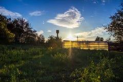 Odlingslottar på solnedgången - polyetentunnel som ett plast- växthus i en odlingslott med växande grönsaker på solnedgången Royaltyfria Bilder