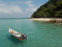 Odludna łódź w szmaragdzie nawadnia, Pulau Kapas wyspa zdjęcia stock